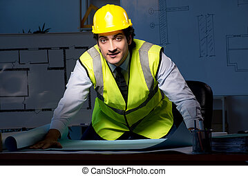 Young construction architect working on project at night