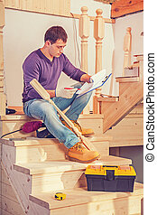 young construction contractor sitting on wooden ladder holding c