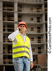 Young construction engineer talking by phone on building...
