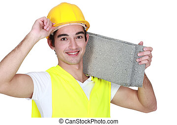 Young construction worker carrying a breeze block.
