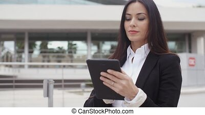 Young contemplative businesswoman holding her tablet in her...
