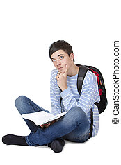 Young contemplative male student sitting on floor with book