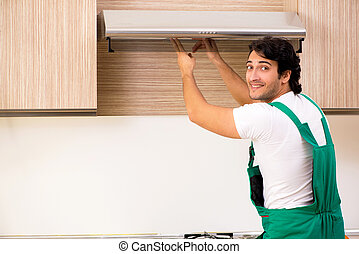 Young contractor repairing air-conditioner in kitchen