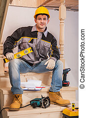 young contractor sitting on wooden ladder holding constructionh level