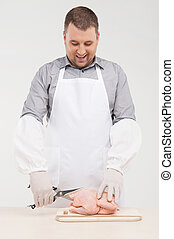 young cook cutting chicken in half. handsome man standing and smiling behind table