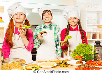 Young cooks holding ingredients for hamburgers