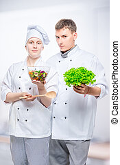 young cooks in suits with salad in hands on gray background