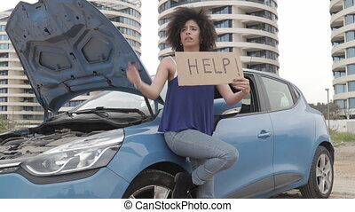 Young cool woman lean on car and holding help sign