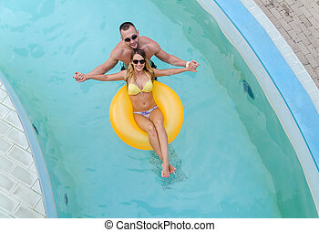 Young cople having fun in the water with yellow mattress.