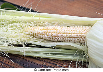 young corn on a wooden table