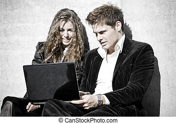 Young Corporate Couple With Laptop In Contrast