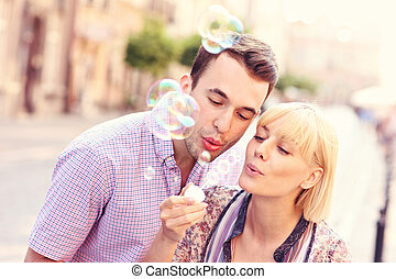 A picture of a young joyful couple blowing bubbles in the city