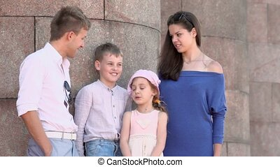 Young couple and pair of little kids stand near colonnade