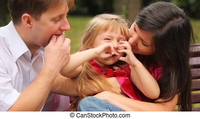 couple and their daughter play game with fingers in park