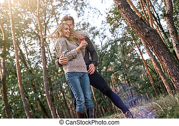 Young couple are dancing in autumn forest.