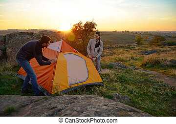Young Couple Assembling the Tent at Sunset in the Mountains. Adventure and Family Travel.