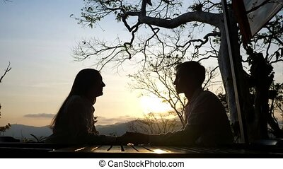 Young couple at a cafe table on a beautiful sunset background