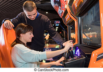 Young couple at arcade driving game