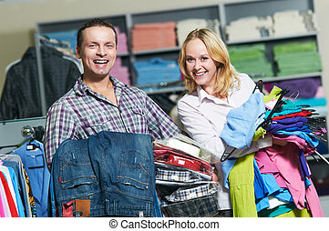 Young couple at clothes shopping - Young couple choosing...