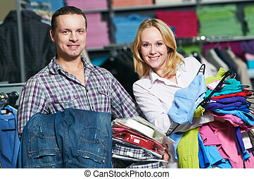 Young couple choosing shirt and necktie during clothing shopping at store