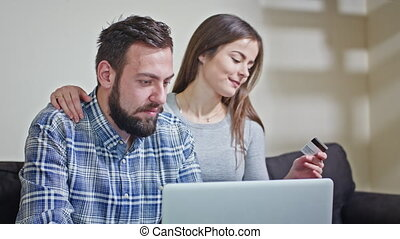 Young Couple at Home Buying on Internet - Young couple at...