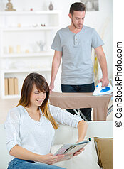 young couple at home man ironing to relieve his wife