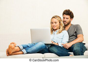 Young couple at home using laptop