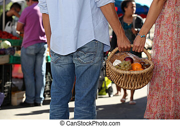 young couple at market buying fruits