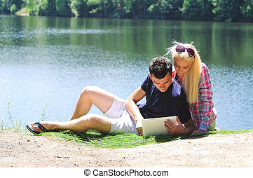 Young couple at notebook in nature