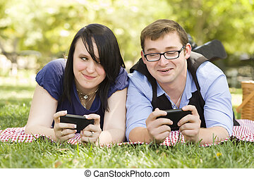 Young Couple at Park Texting Together