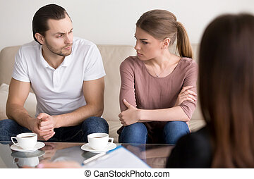 Young couple at psychologist, looking at each other with hate