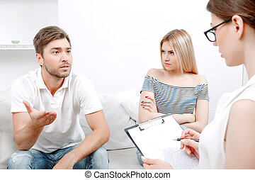 Young couple at psychologist - Young man explaining his...