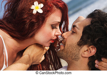 Young couple at the beach about to kiss, intimate setting.