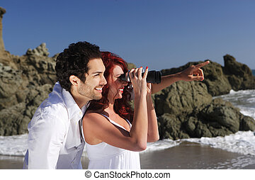 Young Couple at the beach looking through binoculars