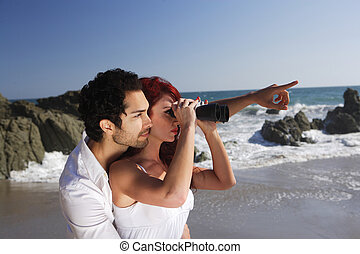 Young Couple at the beach looking through binoculars.