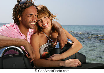 Young couple at the beach stood by convertible car