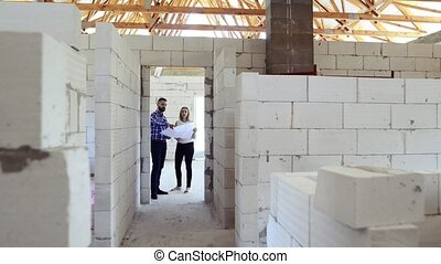 Young couple at the construction site. A man and woman...