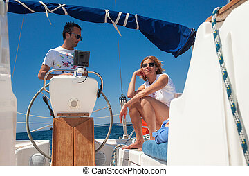 Young couple at the helm of a boat against a blue sky