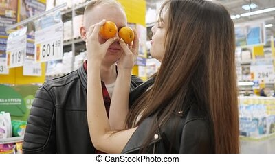 Young couple at the hypermarket. Girl is making funny...