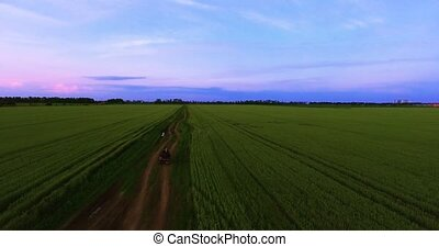 Young couple. ATV moving on a country road. Rural field with...