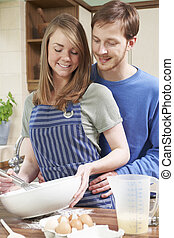Young Couple Baking In Kitchen Together