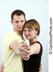 Young couple ballroom dancing with their arms extended and...