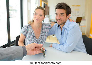 Young couple being passed set of keys