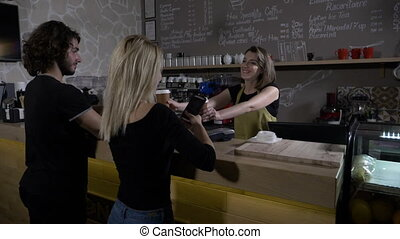 Young couple being served simultaneously by a smiling barista and paying with smartphone technology app in coffee shop in slow motion
