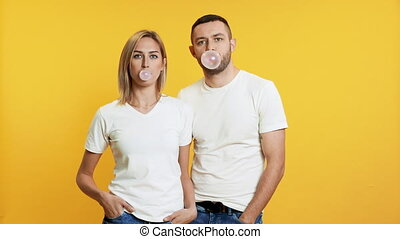 Young couple blowing bubbles with chewing gum on yellow ...
