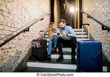 Young couple business people travelers, with suitcases, sitting at the stairs and using mobile phone