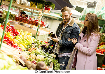 Young couple buying vegetables on a market