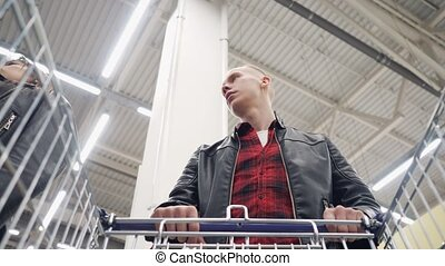 Young couple buys products in a supermarket and puts them in...