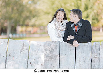 Young couple by the wooden fence