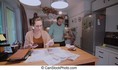 Young couple calculating their domestic budget together in the kitchen, try to safe money, having stresses.